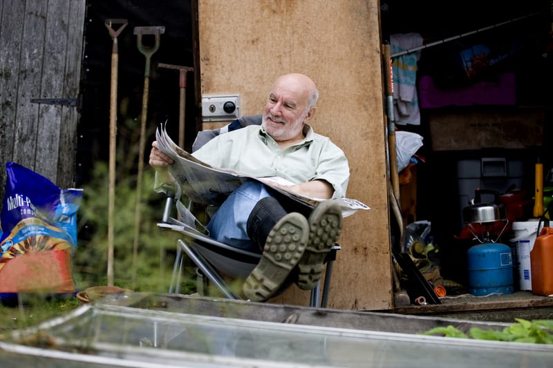 a-senior-man-having-a-break-on-an-allotment-reading-a-newspaper | PHC Tennessee