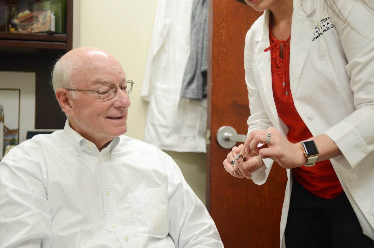 patient looking at hearing aids | PHC Tennessee